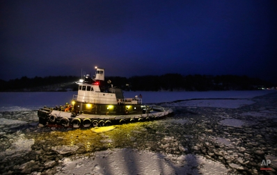The Aegean Sea, a 79-foot tug boat piloted by Capt. Steve Driscoll, uses its 2,200-horsepower engine to break through ice on its way to push a barge out of the Royal River early Friday morning, Jan. 30, 2015, in Yarmouth, Maine. (AP Photo/Robert F. Bukaty)