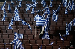A man places Greek flags on seats for New Democracy party supporters ahead of Prime Minister's Antonis Samaras pre-election speech at the Taekwondo Indoor Stadium in southern Athens on Friday, Jan. 23, 2015. All opinion polls on Sunday's closely-watched national election agree: The radical left opposition Syriza party, which has vowed to rewrite the terms of Greece's international bailout, enjoys a lead of at least 4 percentage points over Prime Minister Antonis Samaras' conservatives. (AP Photo/Petros Giannakouris)