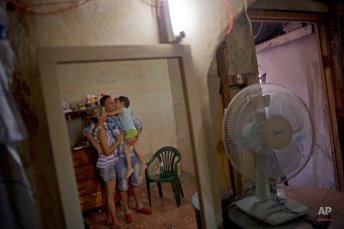 A day after his release, Wilberto Parada, 42, center, is reflected in a mirror with his son and wife, during an interview, in his home in Havana, Cuba, Friday, Jan. 9, 2015. (AP Photo/Ramon Espinosa)