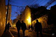 People walk up and down a steep street next to the Gloria funicular tracks in Lisbon, Monday, Jan. 12, 2015. Gloria, Bica and Lavra are the three street funiculars in the capital that help locals and tourists move up and down its hilly districts. (AP Photo/Francisco Seco)