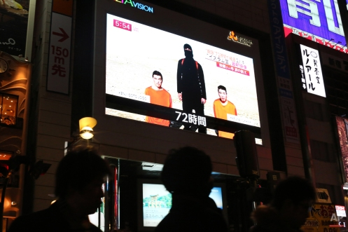 """A TV news program reports two Japanese hostages held by the Islamic State group in Tokyo, Friday, Jan. 23, 2015. Militants affiliated with the Islamic State group have posted an online warning that the """"countdown has begun"""" for the group to kill a pair of Japanese hostages. (AP Photo/Eugene Hoshiko)"""