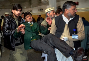 Pakistani volunteers carry a student injured in the shootout at a school under attack by Taliban gunmen, at a local hospital in Peshawar, Pakistan,Tuesday, Dec. 16, 2014. (AP Photo/Mohammad Sajjad)