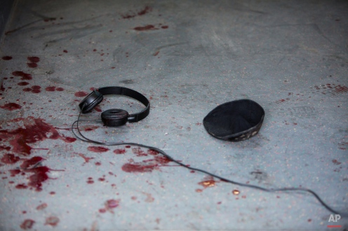 """A Jewish cap and headphones lie in blood stains on the floor at a bus stop after a stabbing attack in Tel Aviv, Israel, Wednesday, Jan. 21, 2015. A Palestinian man stabbed nine people, injuring several seriously, on a bus in central Tel Aviv before he was chased down, shot and arrested, Israeli police said Wednesday, describing the assault as a """"terror attack"""" in the latest in a spate of violence, the worst Israel has seen in almost a decade. (AP Photo/Oded Balilty)"""