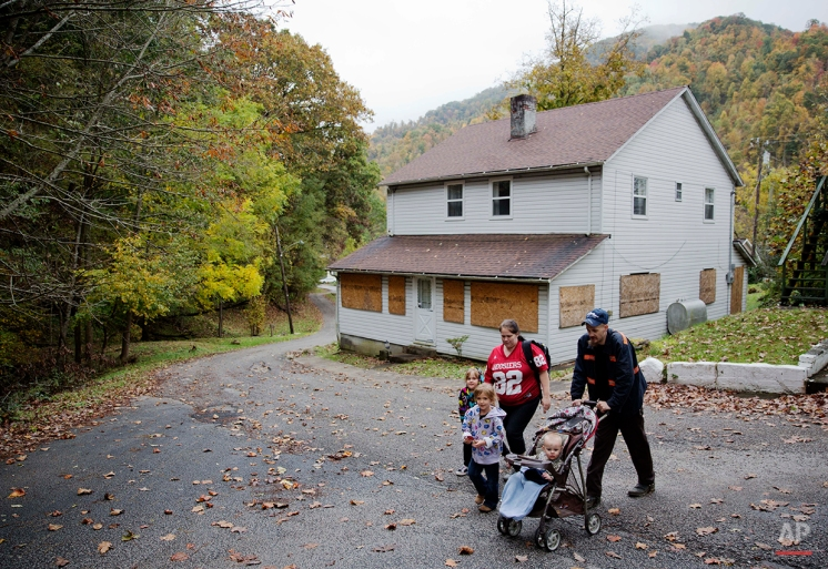 In this Oct. 16, 2014 photo, unemployed coal miner Jeremy Adams, 26, right, walks past a boarded up home with his 15-month-old son Christopher, wife Tiffany Cox, rear, and her daughter Sara, 6, front and Peyton, 5, in Lynch, Ky. (AP Photo/David Goldman)