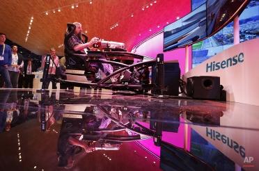 Matt Field uses a race car simulator at the Hisense booth during the International CES, Thursday, Jan. 8, 2015, in Las Vegas. (AP Photo/John Locher)