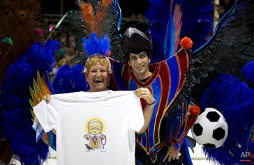 A tourist holds a T-shirt showing Pope Francis wearing a San Lorenzo soccer jersey under his robe as she poses for a photo with a samba school dancer decked out in soccer balls and the team's colors at carnival in Gualeguaychu, Argentina, early Sunday, Jan. 11, 2015. (AP Photo/Natacha Pisarenko)
