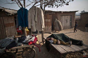 A Pakistani child who was displaced with his family from tribal areas lies next to his grandfather sleeping on a piece of wood next to his second hand clothes displayed for sale on a roadside in the outskirts of Islamabad, Pakistan, Friday, Jan. 2, 2015. (AP Photo/Muhammed Muheisen)