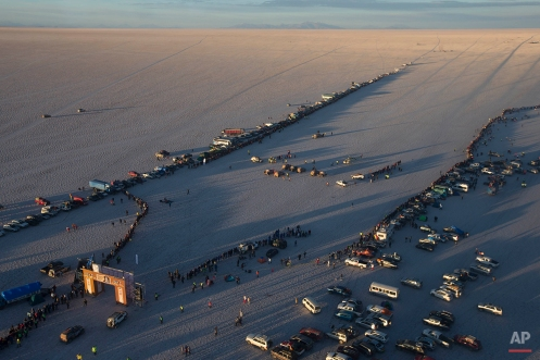 People gather on the Uyuni salt flats as Dakar competitors line up, center, to start the eighth stage of the Dakar Rally 2015 between Uyuni, Bolivia, and Iquique, Chile, Sunday, Jan. 11, 2015. The race will finish on Jan. 17, passing through Bolivia and Chile before returning to Argentina where it started. (AP Photo/Felipe Dana)