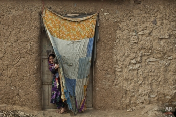 An Afghan refugee girl peeks on through a curtain at the doorway of her family's mud home in a slum on the outskirts of Islamabad, Pakistan, Monday, Jan. 26, 2015. (AP Photo/Muhammed Muheisen)