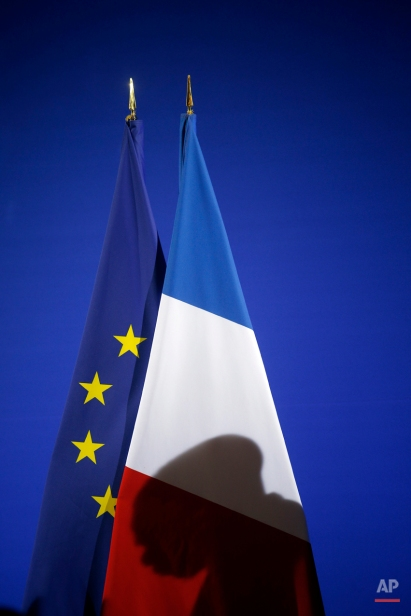 The shadow of Lassana Bathily is cast on the French flag during a citizenship ceremony in Paris, Tuesday, Jan. 20, 2015. Bathily, a Muslim employee born in Mali, has been granted French citizenship and honored as a hero by France's authorities for saving lives during the attack of a kosher supermarket in Paris. (AP Photo/Christophe Ena)
