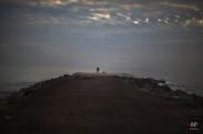 A man stands on a breakwater facing to the Mediterranean sea in Barcelona, Spain, Friday, Jan. 16, 2015. (AP Photo/Emilio Morenatti)