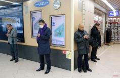 People stand while using smartphones at the building of Shimbashi Station in Tokyo, Wednesday, Jan. 21, 2015. (AP Photo/Shizuo Kambayashi)