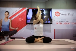 In this Jan. 7, 2015 file photo, a model exercises on the SmartMat, an intelligent yoga mat, at the SmartMat booth at the International CES in Las Vegas. SmartMat costs $297 and will ship in July. (AP Photo/Jae C. Hong)