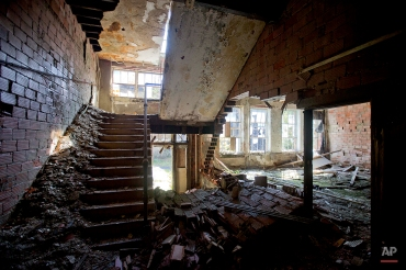 In this Oct. 17, 2014 photo, an entrance to Lynch High School sits in the abandoned building in Lynch, Ky. The community of Lynch, built as a company town in 1917 by U.S. Coal and Coke, a subsidiary of U.S. Steel, was at the time the largest coal camp in the world. It was built to house the many workers and their families mining the coal to be used by U.S. Steel. The population peaked to around 10,000 but has since diminished to roughly 747 according to a 2010 census. U.S. Steel started to sell the houses to the residents as it looked to move its coal production to a newer plant in Corbin, Ky., in 1955. Coal production decreased over the years as the use of oil and natural gas increased and the progression of less labor intensive coal mining techniques meant fewer employees needed. As population numbers dropped, the school closed in 1981 as the county consolidated districts and now sits abandoned up the street from the old mines. (AP Photo/David Goldman)
