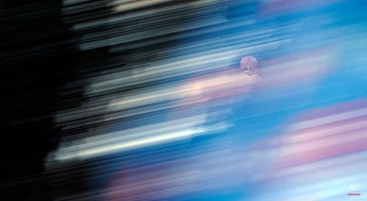 In this picture taken with a longtime exposure Austria's Stefan Kraft soars during the trial jump of the fourth stage of the four hills ski jumping tournament in Bischofshofen, Austria, on Tuesday, Jan. 6, 2015. (AP Photo/Matthias Schrader)