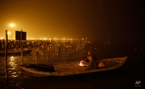 Boatmen keep warm by a bonfire early morning at Sangam, the confluence of the Rivers Ganges, Yamuna and mythical Saraswati, on the first day of Magh Mela Festival in Allahabad, India, Tuesday, Jan. 14, 2014. (AP Photo/ Rajesh Kumar Singh)