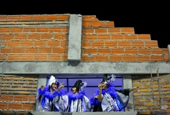 Members of the Ara Yevi samba school perform on a float representing a home in a shantytown during a carnival parade in Gualeguaychu, Argentina, early Sunday, Jan. 11, 2015. The samba school paid tribute to Pope Francis with a four float parade, each of them commemorating different aspects of the Pope's life, including his work with the poor who live in shantytowns. (AP Photo/Natacha Pisarenko)