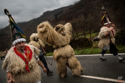 Joaldunaks, some to call them ''Zanpantzar'', take part on the Carnival between of the Pyrenees villages of Ituren and Zubieta, northern Spain, Tuesday, Jan. 27, 2015. In one of the most ancient carnivals in Europe, dating from before the Roman empire, companies of Joaldunak (cowbells) involving the residents of two towns, Ituren and Zubieta, parade the streets costumed in sandals, lace petticoats, sheepskins around the waist and shoulders, coloured neckerchiefs, conical caps with ribbons and a hyssop of horsehair in their right hands and cowbells hung across their lower back. (AP Photo/Alvaro Barrientos)