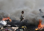 A Filipino boy runs amid black smoke billowing from electrical wires being burned by scavengers at a dumpsite in Manila, Philippines on Thursday, Jan. 8, 2015. Scavengers earn about P150 (US $3) a day by selling recyclable scraps, copper and other metals they find in the heap of garbage. (AP Photo/Aaron Favila)
