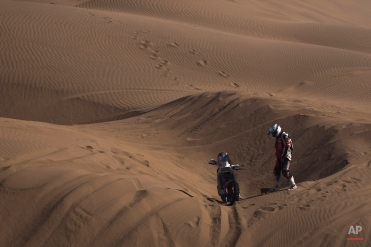 KTM rider Alberto Brioschi, from Italy, stands next to his motorbike stuck in the sand during the fourth stage of the Dakar Rally 2015 between Chilecito, Argentina and Copiapo, Chile, Wednesday, Jan. 7, 2015. The race will finish on Jan. 17, passing through Bolivia and Chile before returning to Argentina where it started. (AP Photo/Felipe Dana)