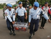 Indonesian air force personnel carry the flight data recorder of the ill-fated AirAsia Flight 8501 that crashed in the Java Sea, at the airport in Pangkalan Bun, Indonesia, Monday, Jan. 12, 2015. Divers retrieved one black box Monday and located the other from the AirAsia plane that crashed more than two weeks ago, a key development that should help investigators unravel what caused the aircraft to plummet into the Java Sea. (AP Photo/Achmad Ibrahim)