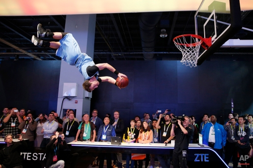 A basketball stunt performer makes a dunk off a trampoline at the ZTE booth during the International CES Wednesday, Jan. 7, 2015, in Las Vegas. (AP Photo/John Locher)