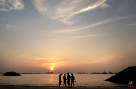 Boys watch the sun rise, Tuesday Jan. 27, 2015 along the eastern coast of Singapore. According to Singapore's National Parks Board, East Coast Park attracts more than seven million visitors a year. (AP Photo/Wong Maye-E)