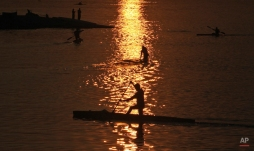 Indians paddle their canoes as the sun sets at the Hussain Sagar Lake in Hyderabad, India, Friday, Jan. 2, 2015. The lake promenade is a busy thoroughfare that provides boating and other water sports facilities. (AP Photo/Mahesh Kumar A.)