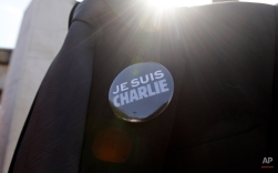 """A man in suit wears a """"Je Suis Charlie"""" (I am Charlie) button, during a gathering in solidarity with victims of the recent Paris terrorist attacks, at the Plaza de Francia in Panama City, Monday, Jan. 12, 2015. A group of foreign residents and Panamanian citizens gathered to protest against the recent terrorist attacks in France. (AP Photo/Arnulfo Franco)"""