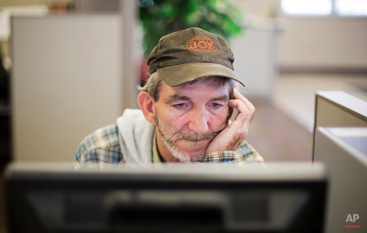 """In this Oct. 20, 2014 photo, unemployed coal miner Eddie Jones looks for jobs on a computer at the Kentucky Career Center in Harlan, Ky. With no computer at home, he goes to the employment office two or three times a week to see what's available. In the meantime, Jones has been making do with odd jobs, painting, digging ditches, mowing grass. """"Just something to pick up 40 or 50 bucks to pay a water bill,"""" he says. Jones was on unemployment for 26 weeks. He is angry that Congress failed to pass an extension. """"They've bailed out every entity in the country,"""" he says. """"The banking industry. The airline industry. The car industry. Everybody but the American worker."""" (AP Photo/David Goldman)"""