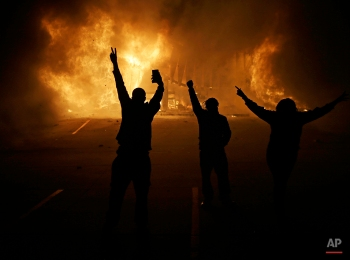 People watch as stores burn Tuesday, Nov. 25, 2014, in Ferguson, Mo. A grand jury has decided not to indict Ferguson police officer Darren Wilson in the death of Michael Brown, the unarmed, black 18-year-old whose fatal shooting sparked sometimes violent protests. (AP Photo/David Goldman)