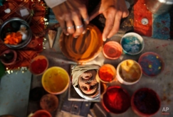 """A Hindu holy man is reflected on a mirror as he prepares a bowl of vermillion powder for devotees near """"Sangam"""", the confluence of holy rivers of Ganges, Yamuna and the mythical Saraswati, during the annual traditional fair of Magh Mela in Allahabad, in the northern Indian state of Uttar Pradesh, India, Tuesday, Jan. 6, 2015. Hundreds of thousands of devout Hindus are expected to take holy dips at the confluence during the astronomically auspicious period of over 45 days celebrated as Magh Mela. (AP Photo/Rajesh Kumar Singh)"""