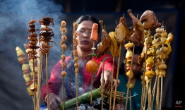 A Mishing tribal woman smokes meat at a temporary stall during an ongoing ethnic food festival as part of festivities to mark Bhogali Bihu festival in Gauhati, India, Saturday, Jan. 10, 2015. Bhogali Bihu is the harvest festival of Assam state and is observed in January every year. (AP Photo/ Anupam Nath)