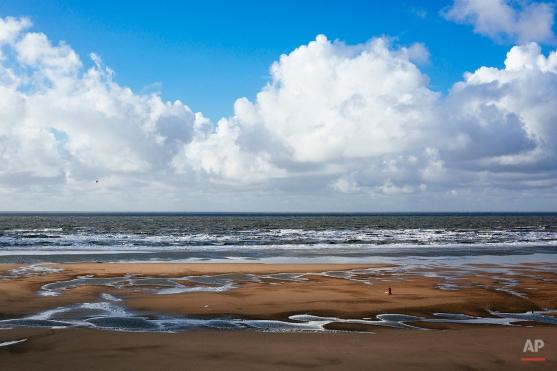 People make their way along the beach in Blackpool, northwest England, Saturday, Jan. 17, 2015. (AP Photo/David Azia)