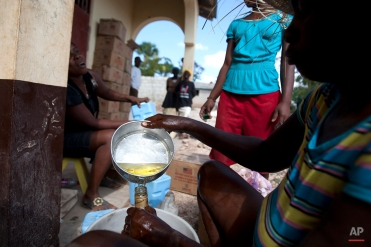 In this Monday, March 24, 2014 photo, an aid worker fills a bottle with cooking oil during distribution of food by the U.N. World Food Program at a local school in Bombardopolis, northwestern Haiti. The agency said it has given food to 164,000 people in the region so far, as well as 6,000 seed kits for farmers. (AP Photo/Dieu Nalio Chery)