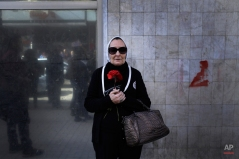 An Egyptian woman holds a red flower during a women's protest in Cairo, Egypt, Thursday, Jan. 29, 2015. Dozens of women have rallied in the Egyptian capital, denouncing the killing of a female protester and blaming the police for her death during a peaceful demonstration last week. (AP Photo/Hassan Ammar)