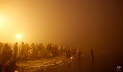 """Hindu devotees bathe early morning at Sangam, the confluence of rivers Ganges and Yamuna, to mark Makar Sankranti festival during the annual traditional fair of """"Magh Mela"""" in Allahabad, India, Wednesday, Jan. 14, 2015. Hundreds of thousands of devout Hindus are expected to take holy dips at the confluence during the astronomically auspicious period of over 45 days celebrated as Magh Mela. (AP Photo/Rajesh Kumar Singh)"""