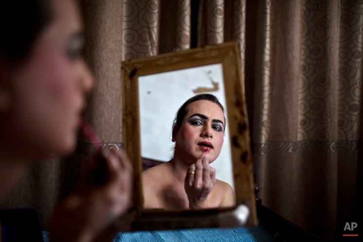 In this Saturday, Jan. 10, 2015 photo, Pakistani Waseem Akram, 27, applies makeup on his face as he prepares himself for a party at a friend's place in Rawalpindi, Pakistan. (AP Photo/Muhammed Muheisen)