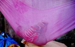 An Indian child rests on a makeshift hammock on a street in Mumbai, India, Tuesday, Jan. 13, 2015. Some 800 million people in the country live in poverty, many of them migrating to big cities in search of a livelihood and often ending up on the streets. (AP Photo/Rafiq Maqbool)