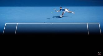Novak Djokovic of Serbia hits a forehand return to Sloveniaís Aljaz Bedene during their first round match at the Australian Open tennis championship in Melbourne, Australia, Tuesday, Jan. 20, 2015. (AP Photo/Lee Jin-man)