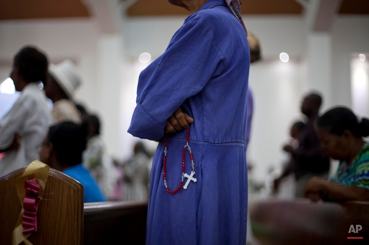A woman holding a rosary, prays during a Mass marking the 5th anniversary of the January 2010 earthquake, during a service held next to the damaged National Cathedral in Port-au-Prince, Haiti, Monday, Jan. 12, 2015. Somber Haitians gathered early Monday to remember the devastating earthquake that left much of the capital and surrounding area in ruins in one of the worst natural disasters of modern times. (AP Photo/Dieu Nalio Chery)