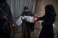 A Pakistani police officer, left, stands guard while a polio worker vaccinates an Afghan refugee child against polio in a slum on the outskirts of Islamabad, Pakistan, Wednesday, Jan. 21, 2015. Militants have spread a rumor among ultraconservative parents in Pakistan's deeply religious northwest, saying the polio vaccine will make their children impotent. The vaccine, they claim, is a ploy by the West to limit the world's Muslim population. (AP Photo/Muhammed Muheisen)