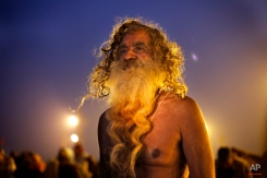 An Indian holy man returns after taking a holy dip at Sangam, the confluence of the rivers Ganges and Yamuna, during the annual month long Hindu religious fair 'Magh Mela', in Allahabad, India, Monday, Jan. 5, 2015. (AP Photo/ Rajesh Kumar Singh)