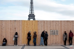 People stand along a fence, at the Trocadero place, near the Eiffel Tower in Paris, Sunday, Jan. 18, 2015. (AP Photo/Thibault Camus)