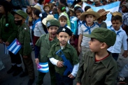 Children dressed as Cuban revolutionaries attend a caravan tribute marking the 56th anniversary of the original street party that greeted a triumphant Fidel Castro and his rebel army, in Regla, Cuba, Thursday, Jan. 8, 2015, Castro and his rebels arrived in Havana via caravan on Jan. 1, 1959, after toppling dictator Fulgencio Batista. The revolutionary leader and former president has not spoken publicly on the historic Dec. 17th US-Cuba detente. (AP Photo/Ramon Espinosa)