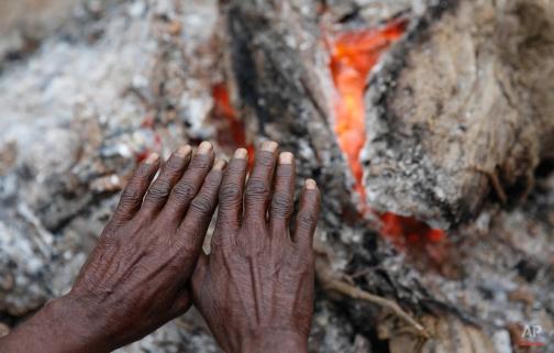 An Indian villager warms himself near a bonfire on a cold morning in Saifai village, in the northern Indian state of Uttar Pradesh, Friday, Jan. 2, 2015. (AP Photo/ Rajesh Kumar Singh)