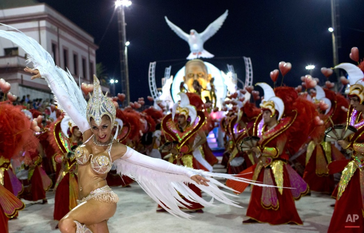 A dancer from the Ara Yevi samba school performs wearing white wings during a carnival parade of dancers and a float decorated with a statue of Pope Francis and a peace dove, as their tribute to the Argentine-born pontiff in Gualeguaychu, Argentina, early Sunday, Jan. 11, 2015. (AP Photo/Natacha Pisarenko)