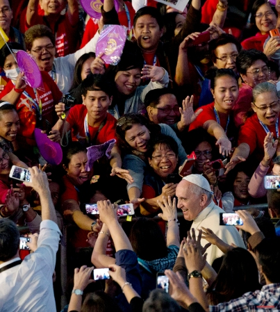 Pope Francis smiles as he arrives at the Mall of Asia arena, in Manila, Philippines, for a meeting with families, on Friday, Jan. 16, 2015. Walking into a packed 20,000-seat arena, Francis greeted and blessed the people who lined his long way to the stage. (AP Photo/Alessandra Tarantino)