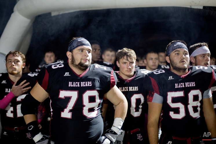 In this Oct. 17, 2014 photo, Harlan County High School football players Zachary Caldwel, left, and Gary Helton, right, wait to take the field before the start of game in Harlan, Ky. Harlan County High opened in 2008, taking in students from dying schools in other parts of the county. The multimillion-dollar facility, with its gleaming hallways and soaring three-story atrium, would put many college campuses to shame. But enrollment is down by about 10 percent a first-year high of 1,150. Since 1980, the county has lost nearly half of its under-35 population since 1980. The 20-24 age group in the area development district that includes Harlan is projected to decline by about a quarter by the year 2050, according to the Kentucky State Data Center at the University of Louisville. (AP Photo/David Goldman)