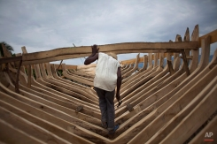 In this May 4, 2013 photo, boat maker Audit Volmar, walks inside the shell of a sail boat he's building on the beach of Leogane, Haiti. The 30-foot-long boats are purchased by smugglers for around $12,000 and then taken to northern Haiti to find passengers. In another major migration trend, Brazil also has become an increasingly common destination for Haitians since the 2010 earthquake. The South American nation initially opened its doors to Haitians seeking asylum, then later said it would issue 1,200 visas annually to allow them to work there for a five-year period. More than 4,000 Haitians have moved to Brazil, both legally and illegally, since the disaster. (AP Photo/Dieu Nalio Chery)